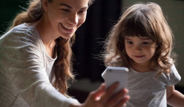 Smiling mother taking selfie on smartphone posing with cute kid daughter, happy young mom laughing making mobile photo with little girl at home, single mommy and child playing having fun with phone